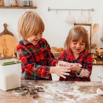 Enfants faisant des biscuits de noël