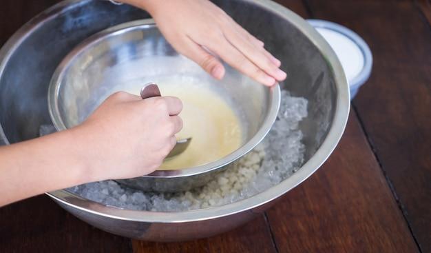 Enfants faisant la crème glacée faite maison avec le bol glacé.