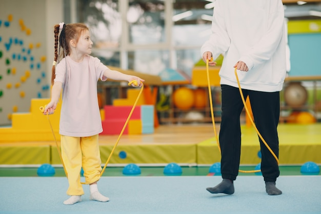 Enfants faisant des exercices avec une corde à sauter dans une salle de sport à la maternelle ou à l'école primaire. concept de sport et de remise en forme pour enfants.