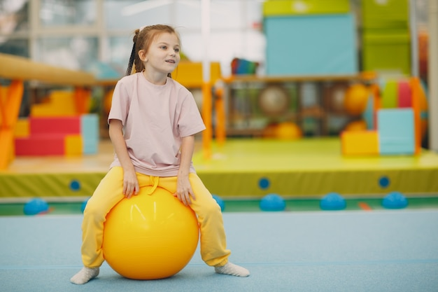 Enfants faisant des exercices avec grosse balle dans la salle de gym à la maternelle ou au concept de sport et de remise en forme pour enfants du primaire