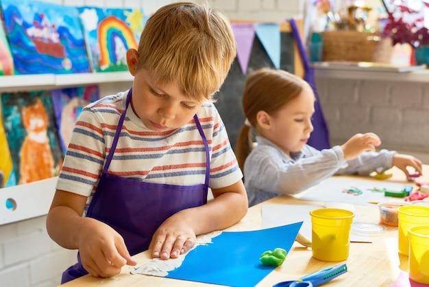 Enfants faisant des images de pâte à modeler
