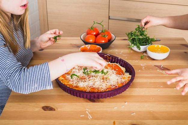 Enfants faisant des pizzas maison ensemble dans la cuisine