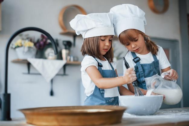 Enfants de la famille en uniforme de chef blanc préparant la nourriture dans la cuisine.