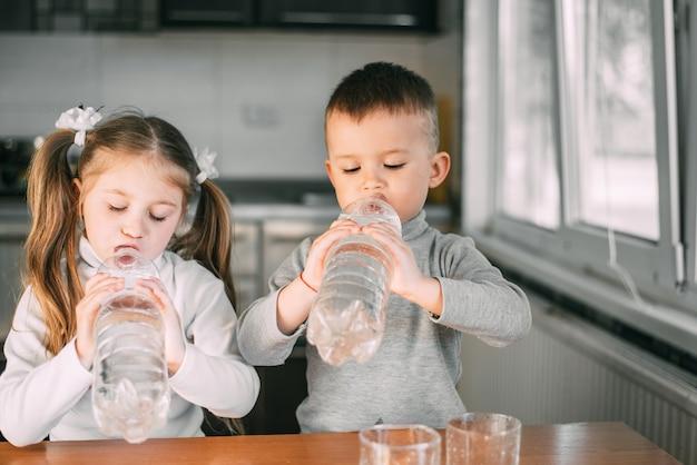 Les enfants fille et garçon boivent de l'eau dans des bouteilles d'un litre avec beaucoup de gourmandise, soif très sucré