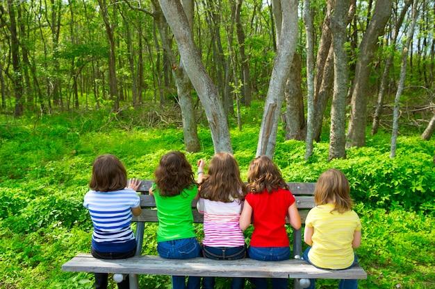 Enfants filles assis sur un banc en regardant forêt