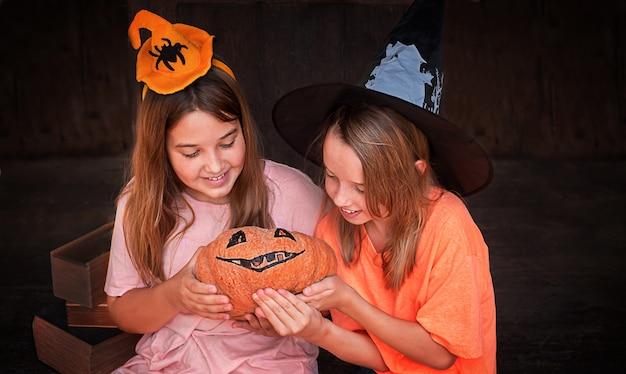 Enfants filles assis avec citrouille jack avec des décorations d'halloween