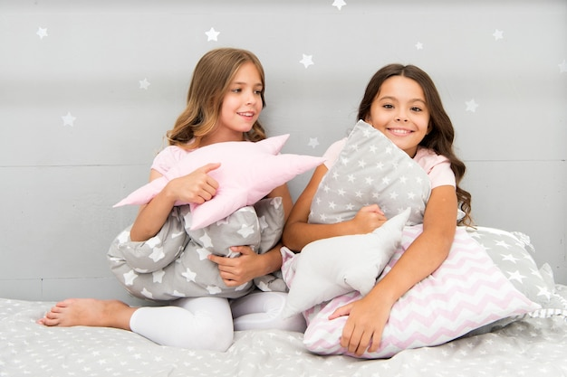 Les enfants des filles embrassent un oreiller mignon. de jolis oreillers pour enfants qu'ils adoreront câliner. trouvez des coussins décoratifs et ajoutez du plaisir à la pièce. maison confortable d'enfance heureuse. adorables coussins pour la chambre de votre enfant.