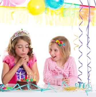 Enfants filles heureux soufflant gâteau fête d'anniversaire