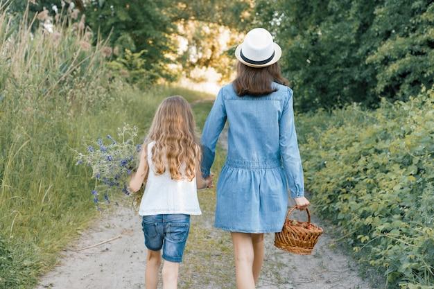 Enfants filles sur la route forestière, tenant par la main. journée d'été ensoleillée, fille tenant le panier avec des baies.