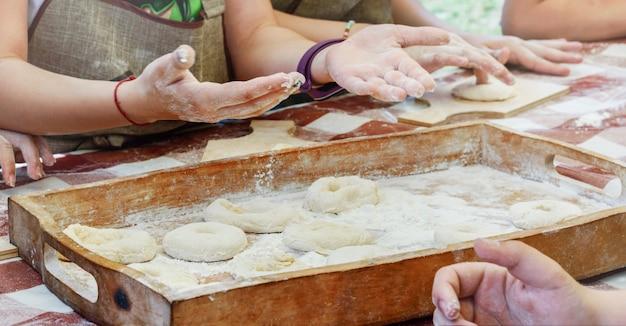 Les enfants font des beignets avec de la pâte et les placent sur des plateaux en bois. master class en pâtisserie.