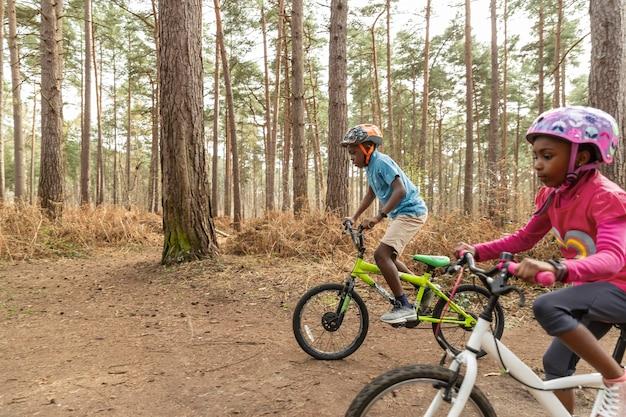 Les enfants font du vélo dans les bois