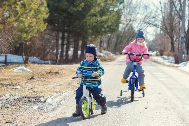 Les enfants font du vélo et du vélo de course le long de la route du village au printemps