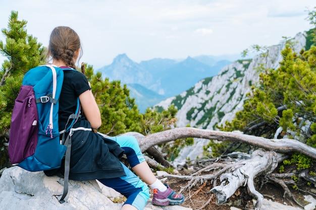 Les enfants font de la randonnée lors d'une belle journée d'été dans les montagnes des alpes en autriche, reposant sur un rocher et admirent une vue imprenable sur les sommets des montagnes. loisirs actifs de vacances en famille avec des enfants. amusement en plein air et activité saine.
