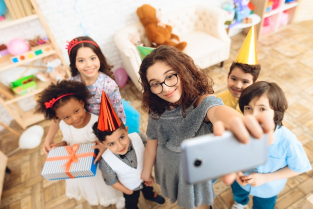 Les enfants font selfie ensemble à la fête d'anniversaire.