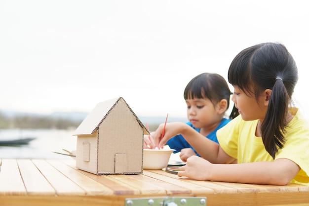Enfants de frère et soeur asiatiques dessinant et peignant la coloration sur le papier