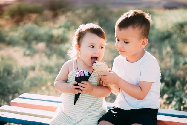 Enfants, frère et soeur sur le banc, manger de la glace est très amusant et mignon