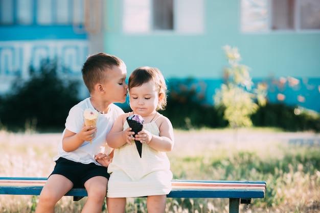 Enfants, frère et soeur sur le banc en train de manger de la crème glacée frère embrasse sa soeur sur la joue très mignon