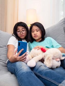 Des enfants de frères et sœurs heureux assis sur un canapé dans le salon parlent avec un parent sur un téléphone portable ensemble, une fille aînée souriante montrant une jolie petite soeur appel vidéo par smartphone parle avec sa famille.
