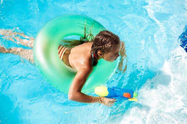 Enfants gais jouant des pistolets à eau, se réjouissant, sautant, nageant dans la piscine.