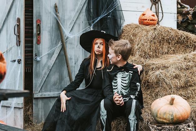Enfants un garçon dans un costume de squelette et une fille dans un costume de sorcière s'amusant à une fête d'halloween sur le porche décoré