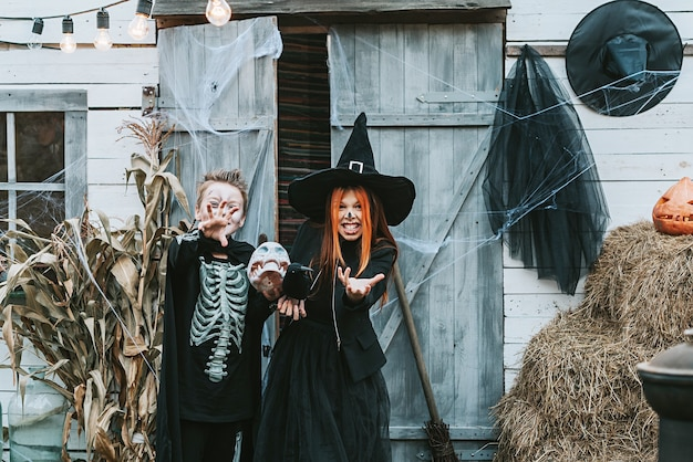 Enfants un garçon dans un costume de squelette et une fille dans un costume de sorcière s'amusant à une fête d'halloween