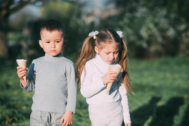 Enfants garçon et fille mangeant de la crème glacée à l'extérieur sur fond d'herbe et d'arbres très doux
