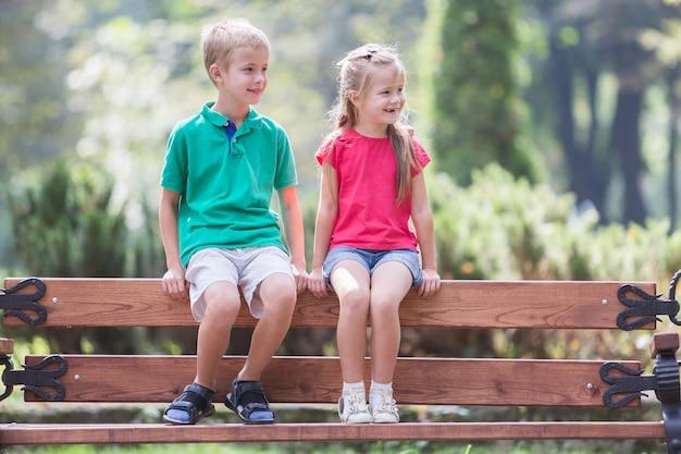 Enfants garçon et fille s'amuser sur un banc dans le parc d'été.