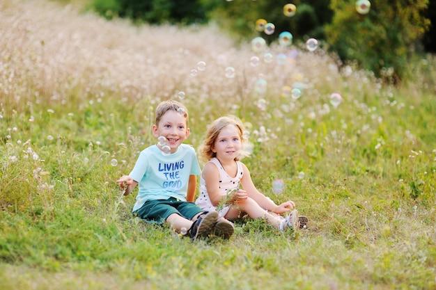 Enfants - un garçon et une fille sont assis dans l'herbe et font des bulles