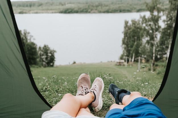 Enfants garçon et fille en tente de camping sur la rive du fleuve dans un paysage pittoresque