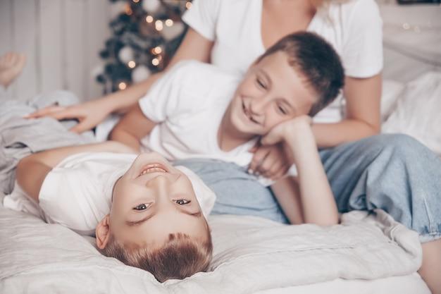 Enfants garçons jouant et riant dans la chambre blanche avec arbre de noël
