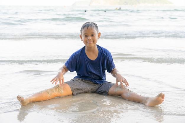 Les enfants garçons jouent joyeusement à la mer sur la plage.