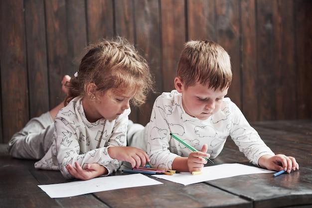 Les enfants gisent par terre en pyjama et dessinent avec des crayons. peinture enfant mignon par des crayons