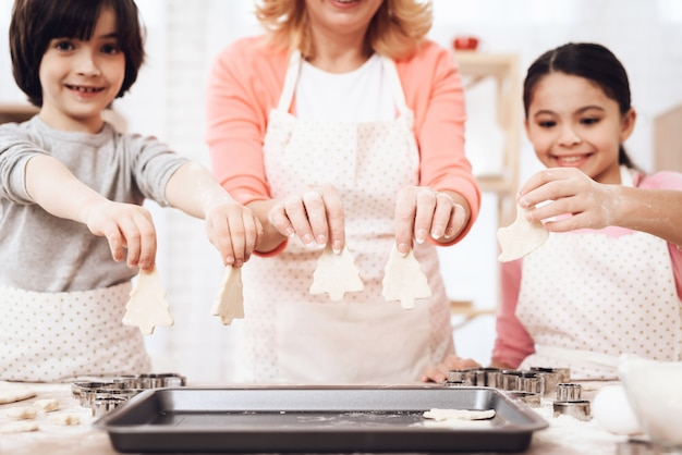Enfants avec la grand-mère mettant des biscuits sur le plateau de cuisson