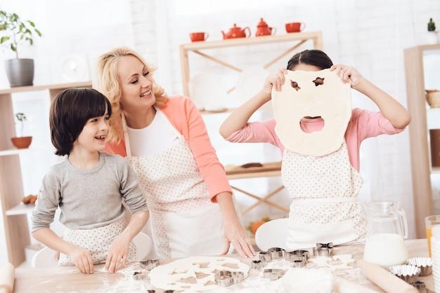 Enfants avec grand-mère s'amusant dans la cuisine