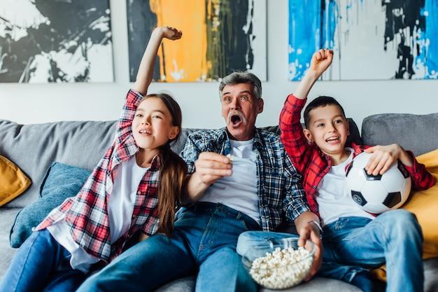 Enfants avec grand-père applaudir pour un match de football