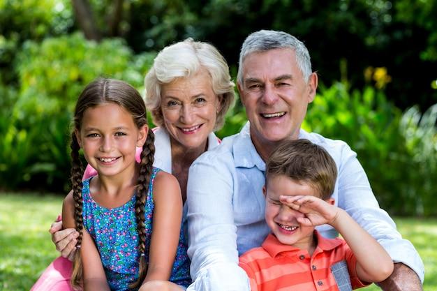 Enfants avec grands-parents assis dans la cour