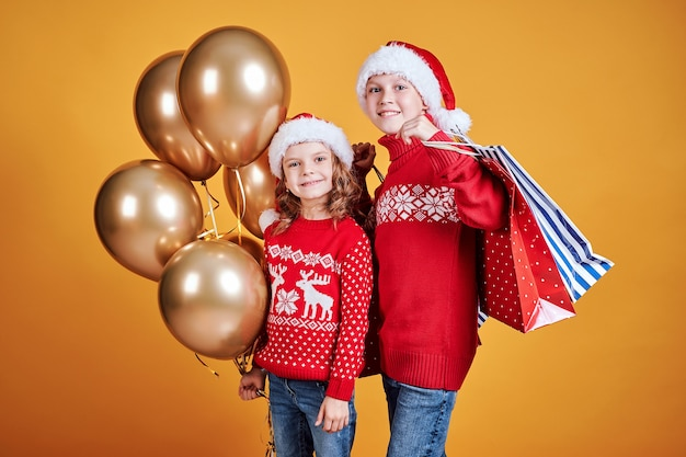 Enfants heureux avec des cadeaux de noël et des ballons