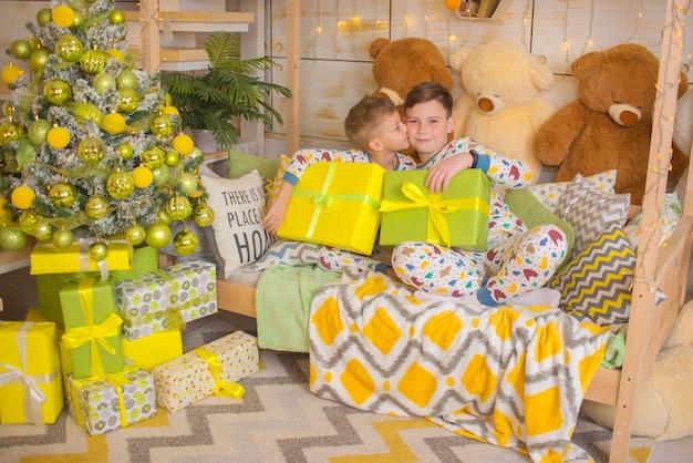 Enfants heureux avec des cadeaux à noël frères près de l'arbre de noël