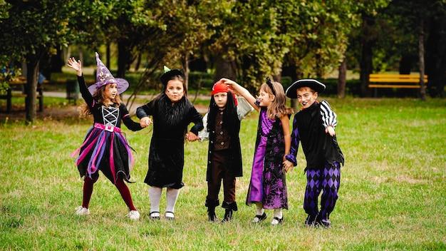 Enfants heureux en costumes d'halloween en cours d'exécution sur la pelouse
