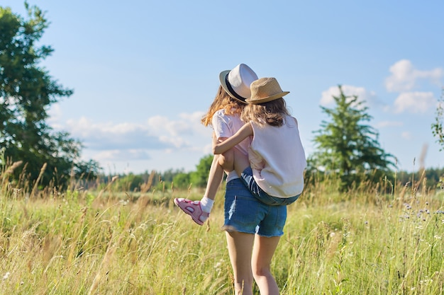 Enfants heureux deux filles sœurs adolescent et plus jeune rire et s'amuser dans le pré, ciel bleu, nature d'été