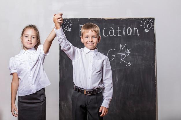 Enfants heureux de l'école élémentaire en ardoise murale de classe