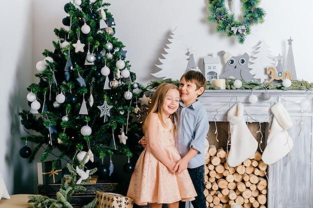 Enfants heureux embrassant et riant en studio avec des décorations de vacances hiver et arbre cristmas.