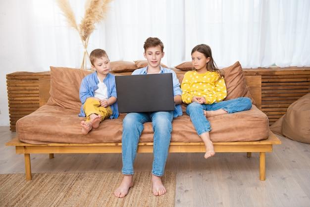 Enfants heureux enfants s'amusant à l'aide d'un ordinateur portable ensemble assis sur un canapé, se détendre à la maison