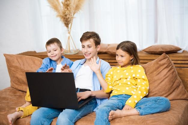 Enfants heureux enfants s'amusant à l'aide d'un ordinateur portable ensemble assis sur un canapé