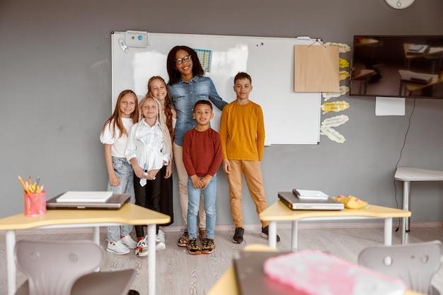 Des enfants heureux et un enseignant posant ensemble en classe