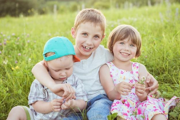 Enfants heureux étreignant assis sur l'herbe verte à l'extérieur