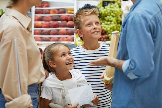 Enfants heureux, faire du shopping avec les parents en supermarché