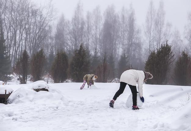 Des enfants heureux font un bonhomme de neige dans un champ enneigé à la campagne.