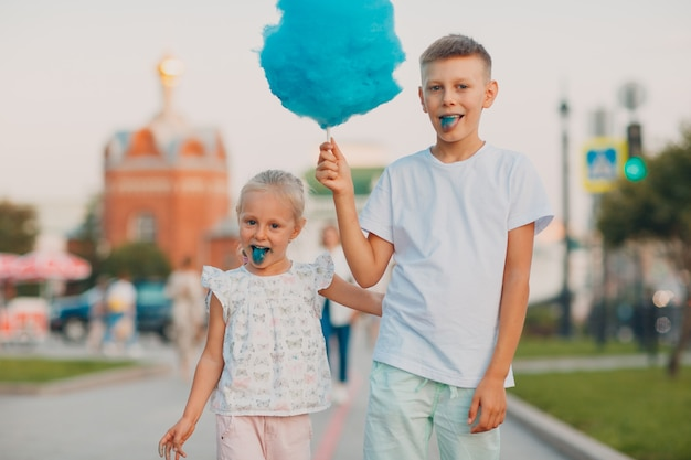 Enfants heureux garçon et fille mangeant de la barbe à papa bleue à l'extérieur.