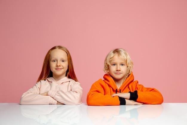 Enfants heureux isolés sur fond de studio rose corail. il a l'air heureux, joyeux, sincère. copyspace. enfance, éducation, concept d'émotions